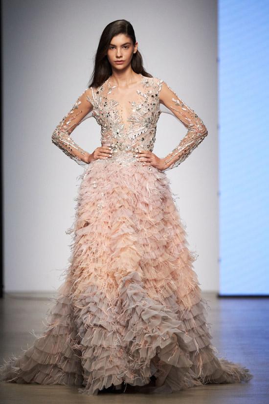 Модель в бежевом вечернем платье с украшениями и перьями