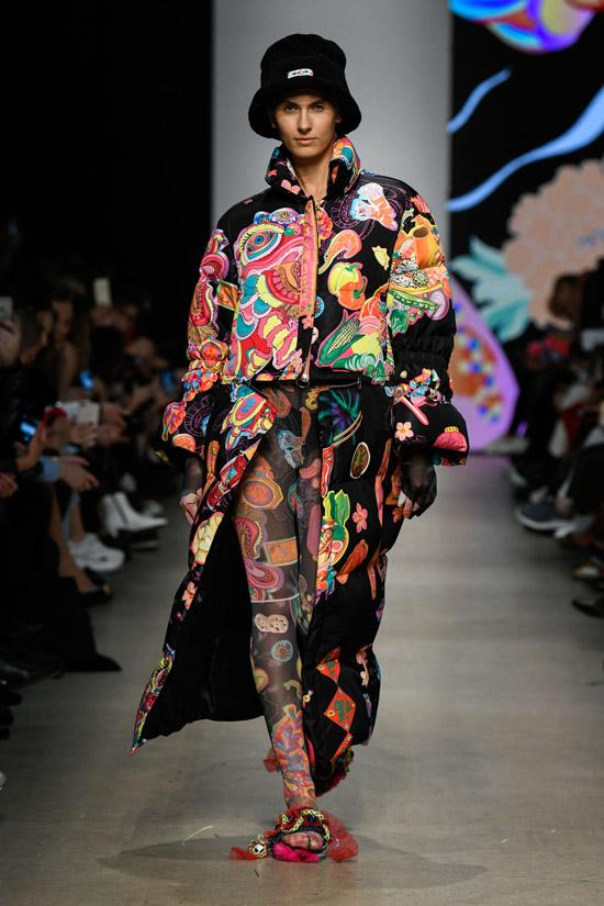 Модель в черной куртке с яркими принтами и черная шапка