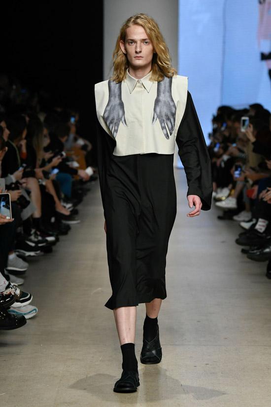 Модель в необычном черно-белом платье с длинными рукавами