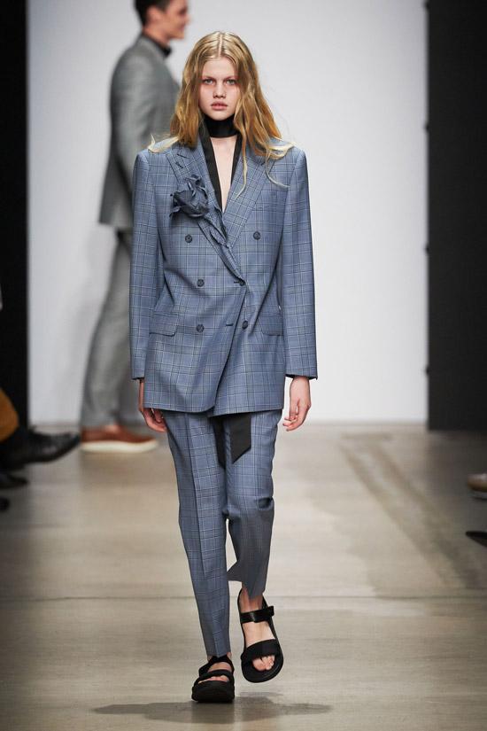 Модель в сером брючном костюме с пиджаком оверсайз и черные сандалии