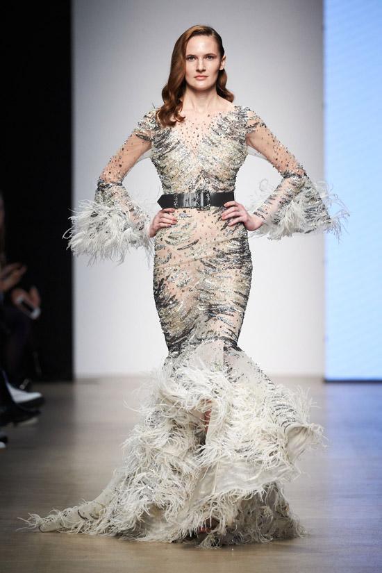 Модель в сером вечернем платье с перьями и черным поясом