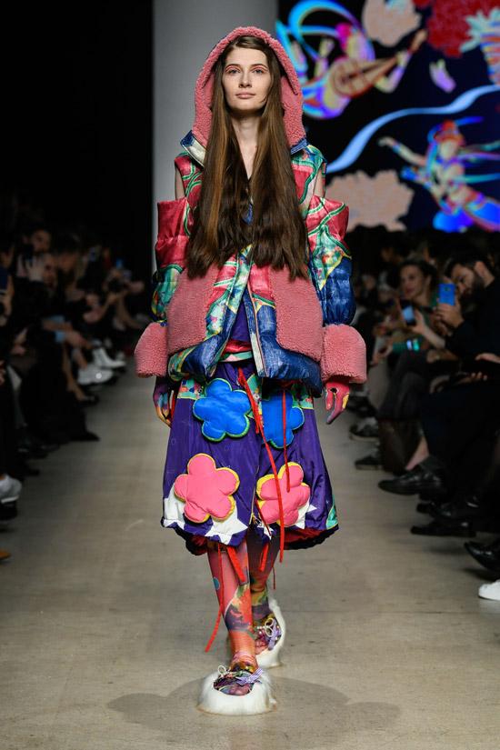 Модель в яркой куртке с капюшоном и теплая юбка