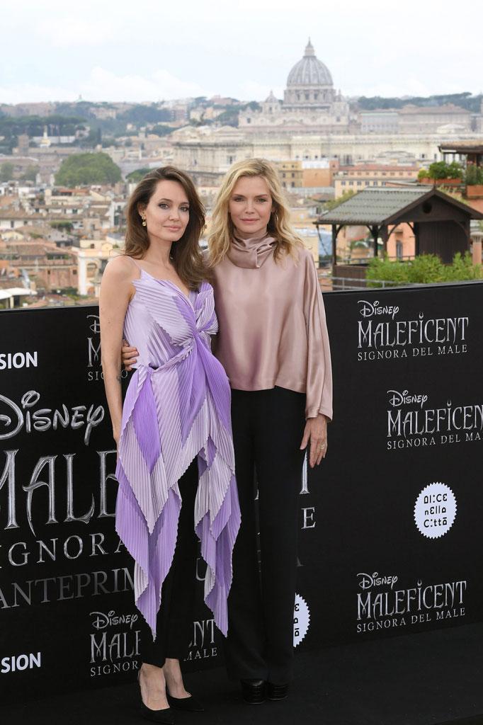 Анджелина Джоли в черных брюках и фиолетвой красивой блузе, рядом Мишель Пфайффер в черных брюках и кремовой блузе