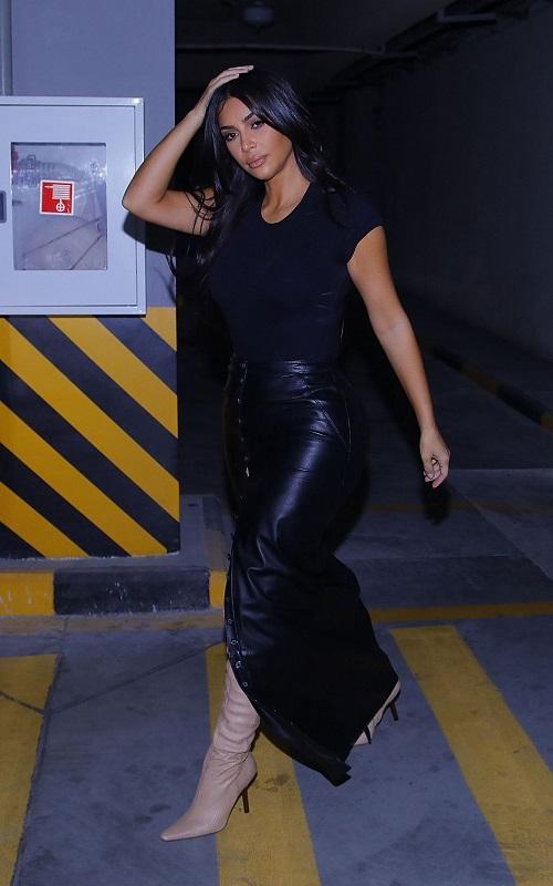 Ким Кардашьян в кожаной длинной юбке, черной футболке и ботильонах