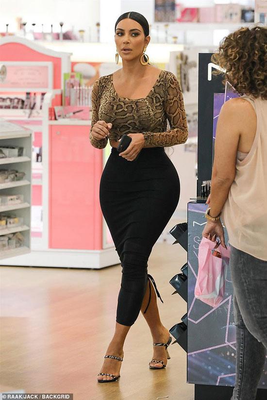 Ким Кардашян в магазине на ней змеиный топ, черная обтягивающая юбка и босоножки