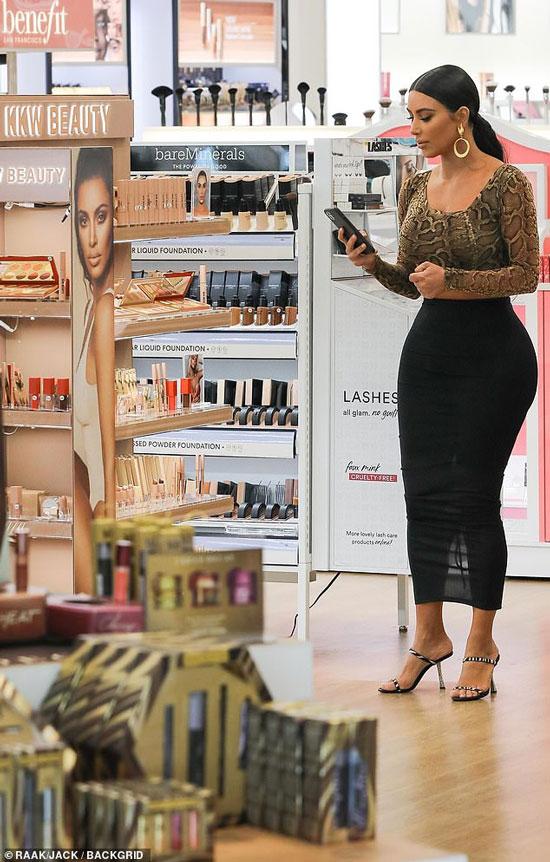 Ким Кардашян в магазине на ней змеиный топ и черная обтягивающая юбка