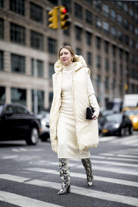 Девушка в белом пуховике, платье свитер и сапоги из змеинной кожи