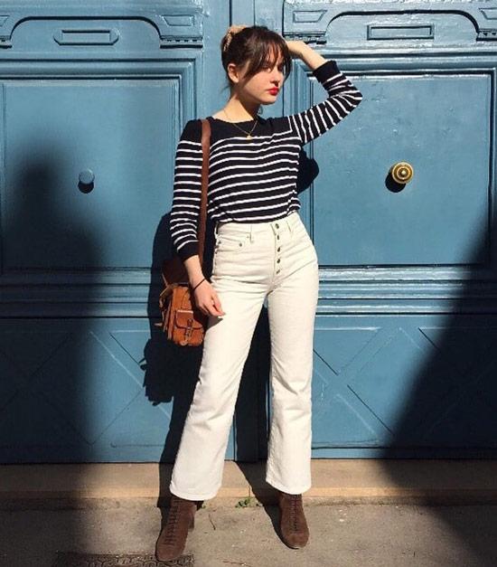 Девушка в белых джинсах, черная кофта в полоску и замшевые ботильоны