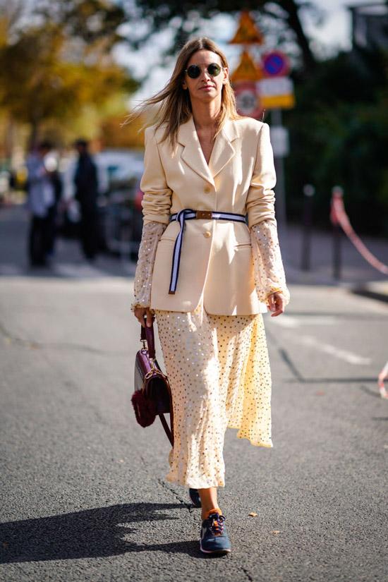 Девушка в бежевой юбке миди, жакет с ремнем и кроссовки