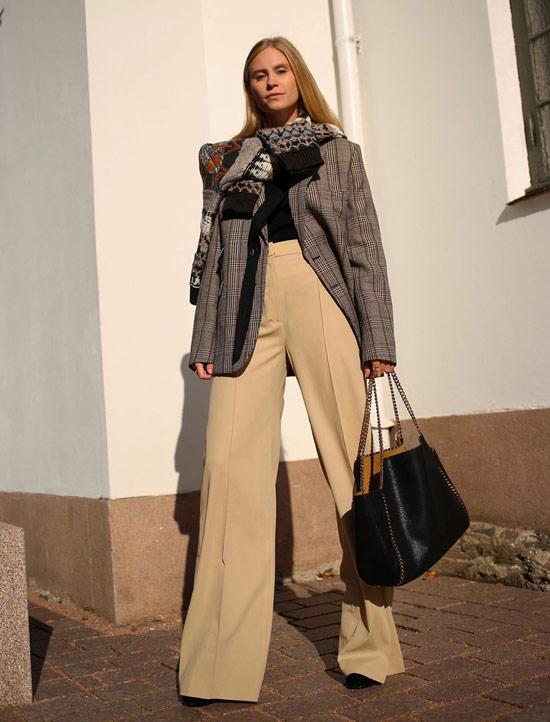 Девушка в бежевых широких брюках, серый блейзер и черная сумка