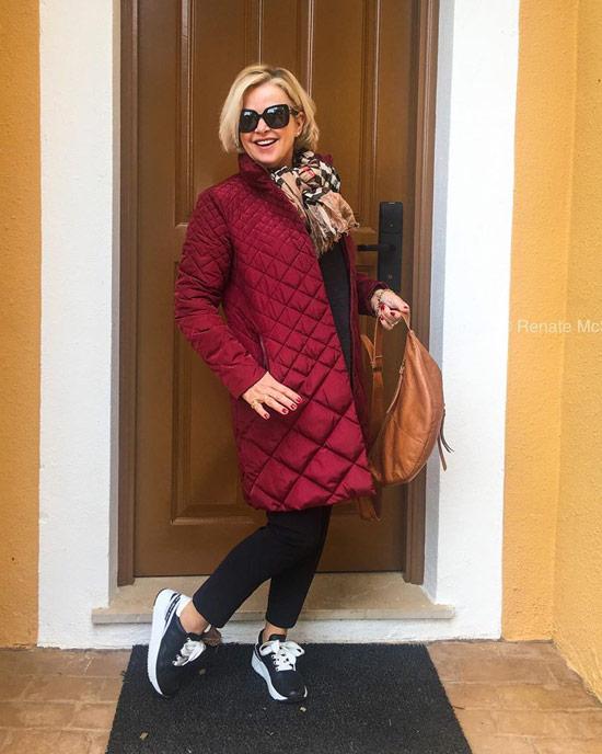 Девушка в бордовом пуховике, черные джинсы и кроссовки