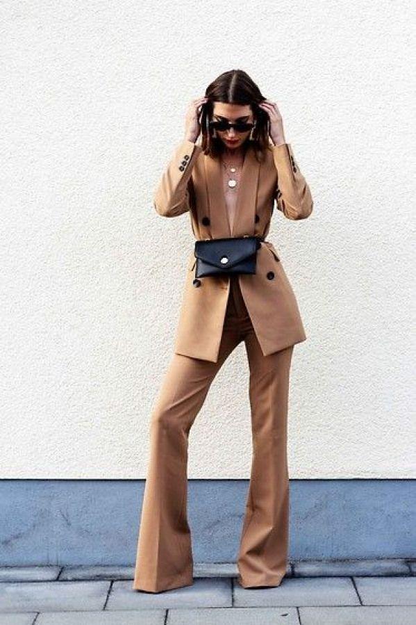Девушка в брючном бежевом костюме и поясная сумка