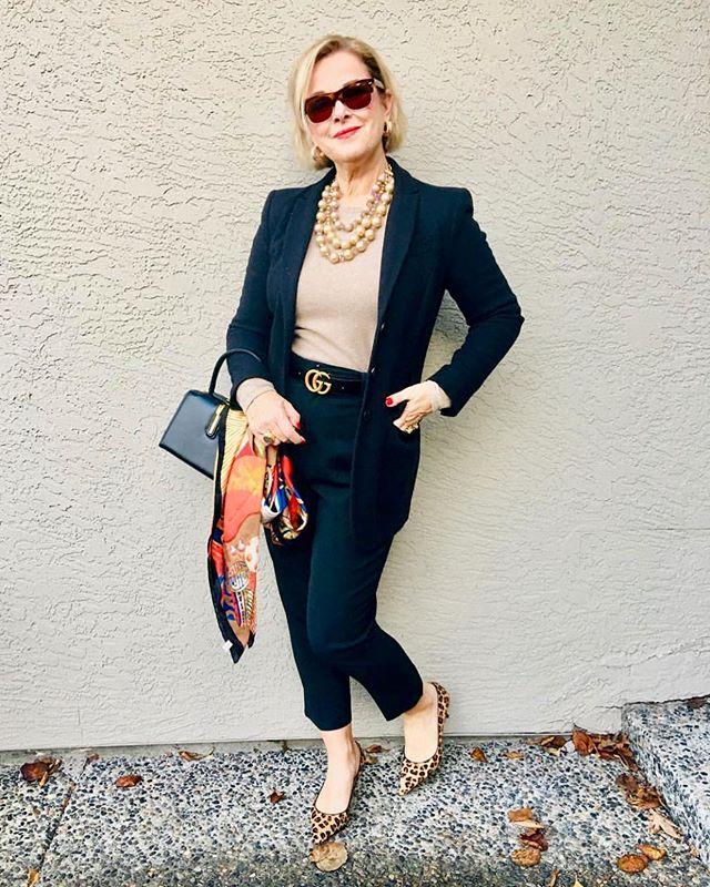 Девушка в черном брючном костюме, бежевый топ и леопардовые туфли