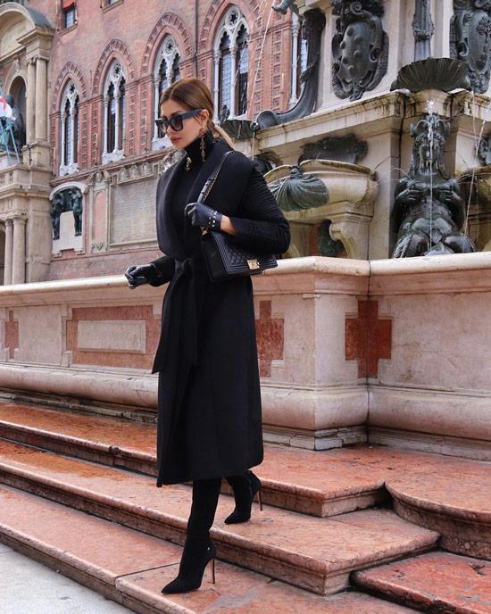 Девушка в черном пальто с поясом, сапоги на шпильке и сумочка