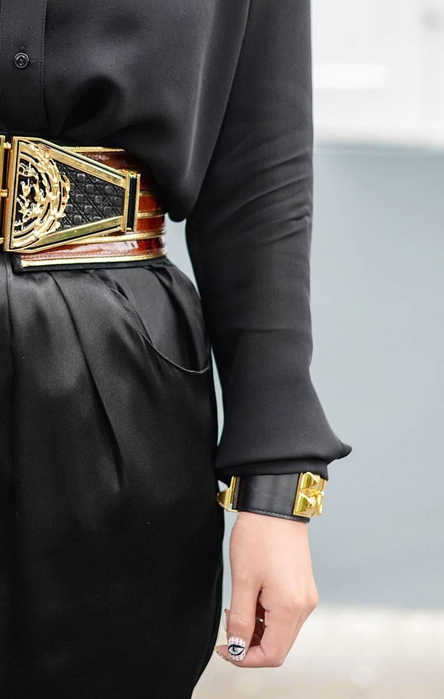 Девушка в черном платье с красивым ремнем и кожаным браслетом