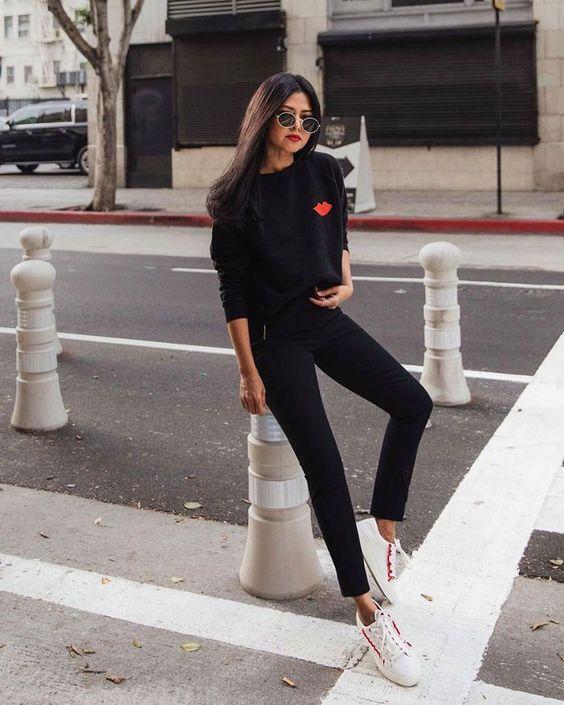Девушка в черных джинсах скинни, черный джемпер и белые кеды