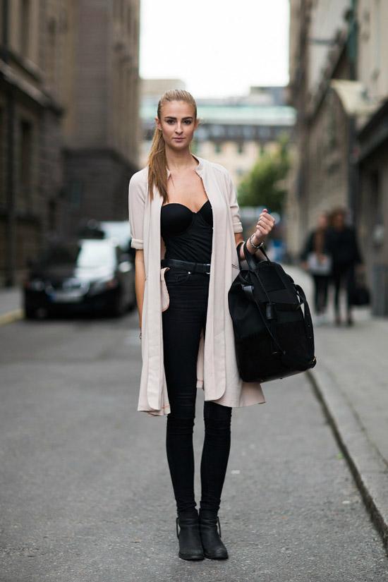 Девушка в черных джинсах скинни, черный топ и светлый кардиган