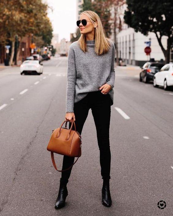 Девушка в черных джинсах скинни, серый свитер и черные ботильоны