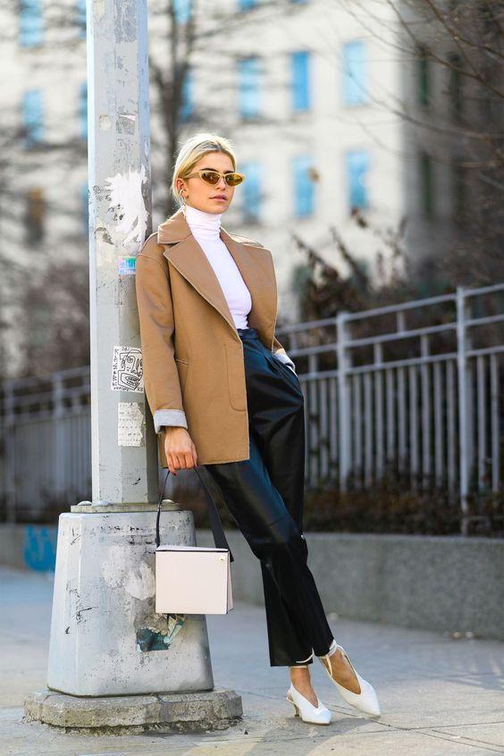 Девушка в черных кожаных брюках, белая водолазка и бежевый жакет