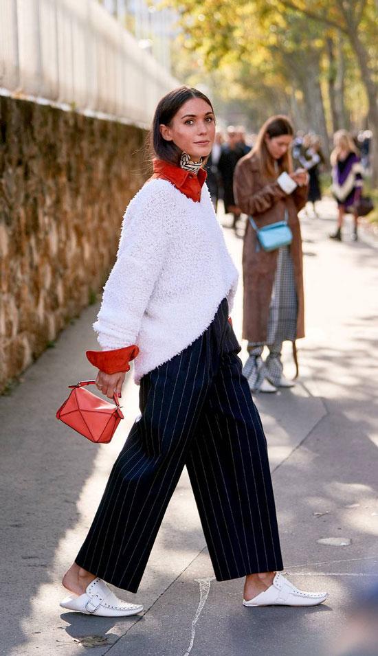 Девушка в черных широких брюках в полоску, белый свитер и лоферы