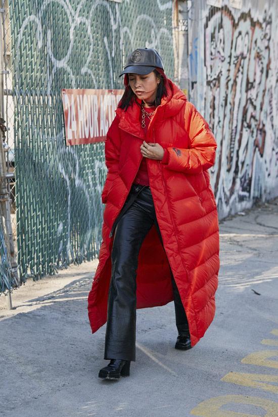 Девушка в длинном красном пуховике, черные кожаные брюки и ботинки