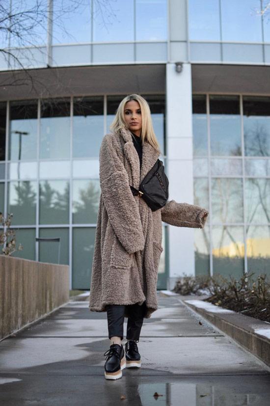 Девушка в длинном пальто тедди и черные кроссовки