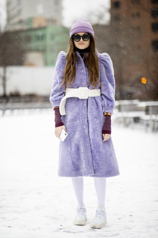 Девушка в фиолетовом меховом пальто с белым поясом, шапочка и кроссовки
