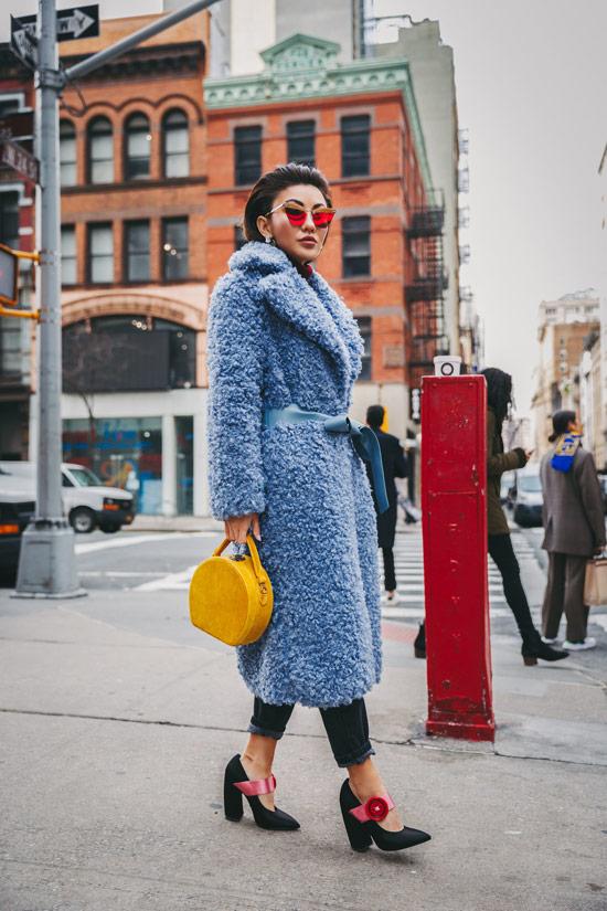 Девушка в голубом плюшевом пальто с поясом и черные джинсы