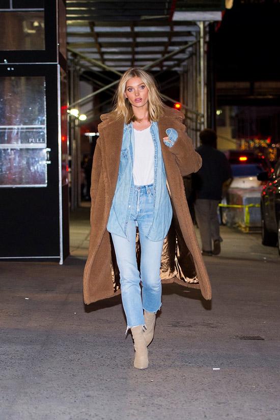 Девушка в голубых джинсах, белая футболка и коричневое плюшевое пальто и светлые ботильоны