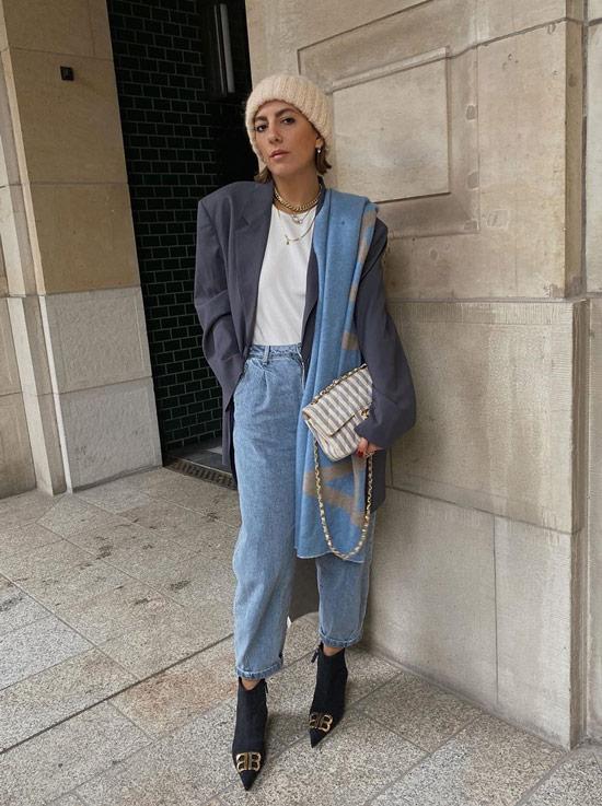 Девушка в голубых джинсах, белая футболка, вязанная шапочка и ботильоны