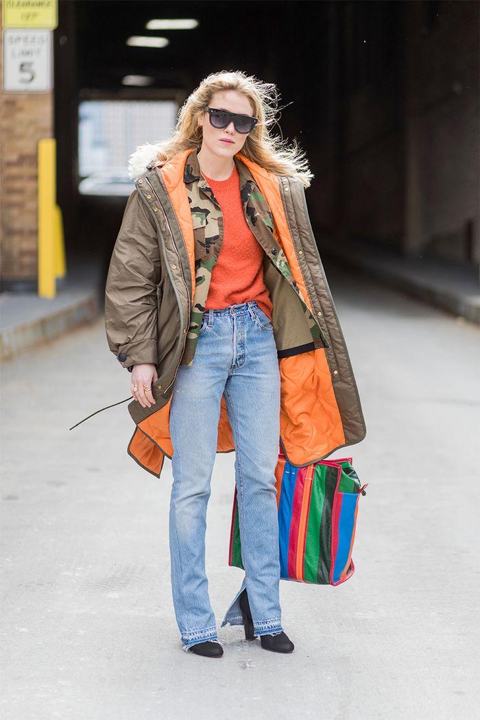 Девушка в голубых джинсах, коричневая парка и оранжевый свитшот