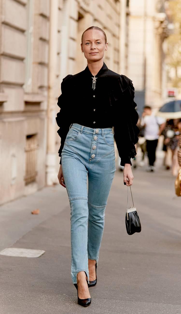 Девушка в голубых джинсах с высокой талией, черная блузка с пышными рукавами и черные туфли