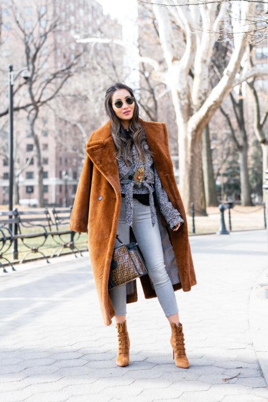 Девушка в голубых джинсах, серая блузка, коричневое пальто тедди и замшевые ботильоны