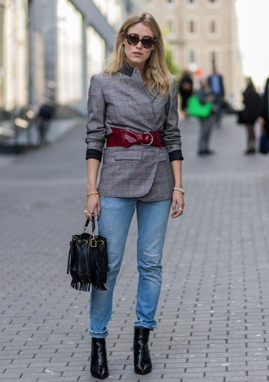 Девушка в голубых джинсах, серый блейзер оверсайз с ремнем и черные ботильоны