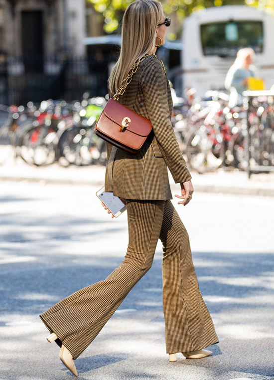 Девушка в коричневом костюме в клетку с брюками клеш и бордовая сумочка