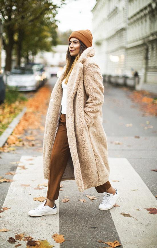 Девушка в коричневых брюках, бежевое тедди пальто и белые кеды