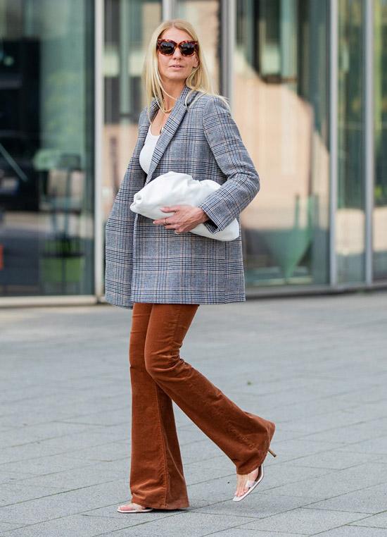 Девушка в коричневых брюках клеш, серый пиджак в клетку и мягкая белая сумка