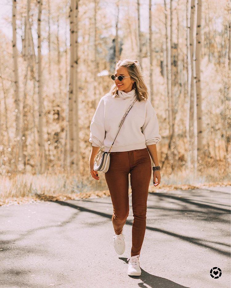 Девушка в коричневых леггинсах, молочный свитер и белые кеды