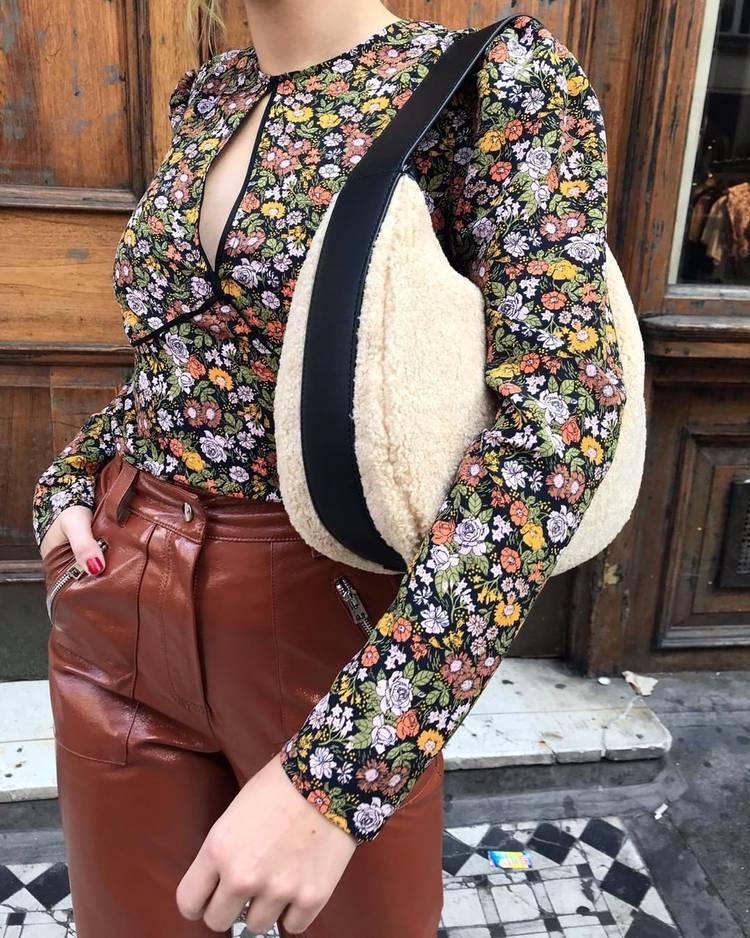 Девушка в кожаных брюках, блузка в цветочек и меховая сумочка