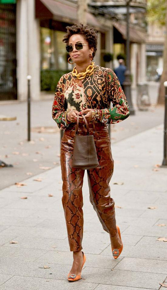 Девушка в кожаных брюках со змеиным принтом и пестрый свитшот, оранжевые босоножки на шпильке