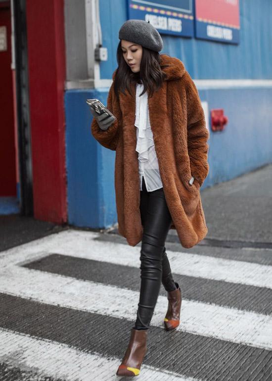 Девушка в кожаных лосинах, белая блузка и коричневое плюшевое пальто