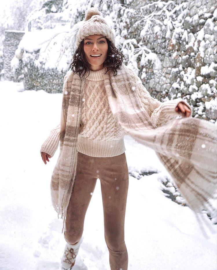 Девушка в леггинсах, бежевый свитер и вязанная шапка