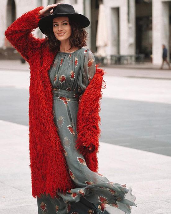 Девушка в легком платье миди и красная шубка с перьями