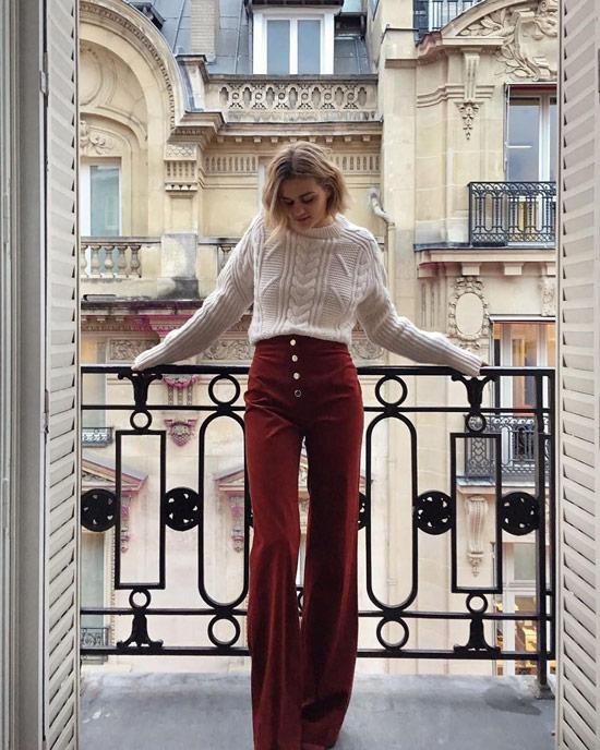 Девушка в оранжевых брюах клеш, белый свитер