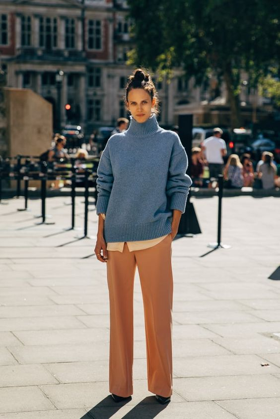 Девушка в прямых бежевых брюках, голубой свитер и черные туфли