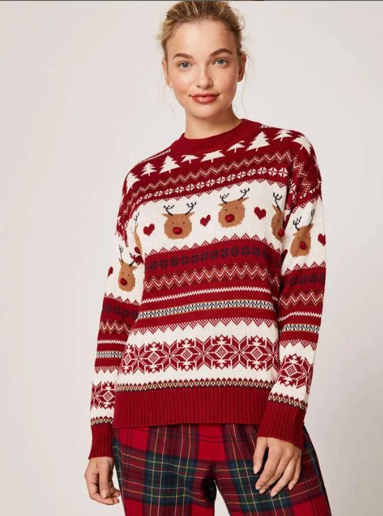 Девушка в красно белом свитере с новогодним принтом и брюках в клетку