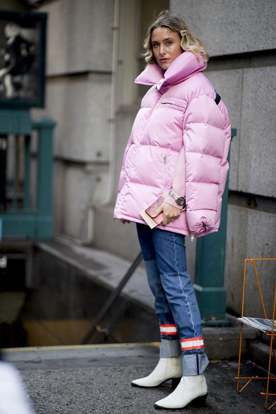 Девушка в розовом пуховике, синие джинсы и белые сапоги