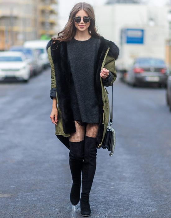 Девушка в сером платье-свитер, зеленая парка и черные ботфорты