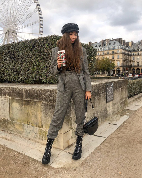 Девушка в сером шерстяном костюме, черные ботинки на шнуровке и сумочка