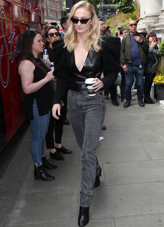 Девушка в серых джинсах, черная блузка и ботильоны